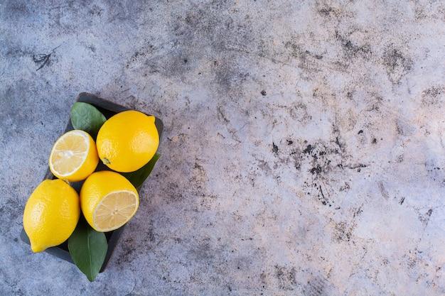 Brede hoekfoto van biologische citroenen op grijs.