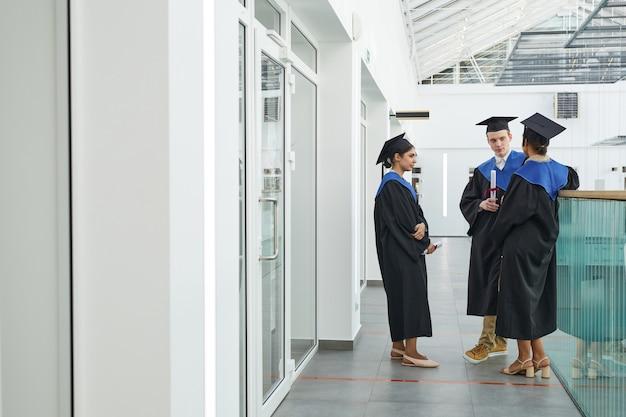 Brede hoekmening bij een groep jongeren die afstudeerjurken dragen die binnenshuis chatten in een modern college-interieur, kopieer ruimte