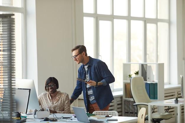 Brede hoekmening bij mannelijke manager die toezicht houdt op werknemer die met computer werkt in modern wit kantoor, kopieer ruimte