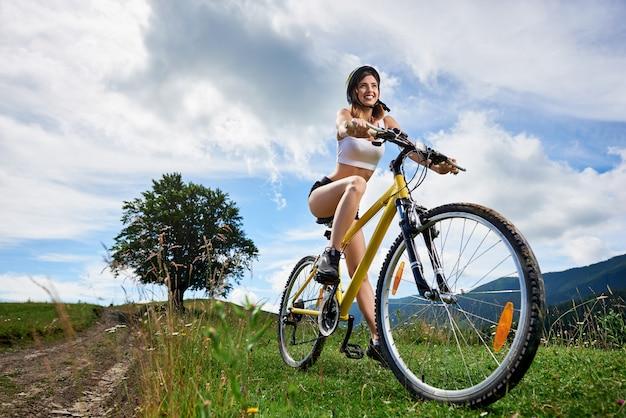 Brede hoekmening die van actieve vrouwelijke fietser op gele fiets op een landelijke sleep in de bergen berijden, die helm dragen. bergen, grote boom en bewolkte hemel. buitensportactiviteiten
