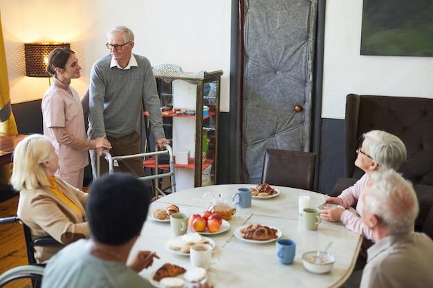 Brede hoekmening op diverse groep senioren die genieten van ontbijt aan eettafel in verpleeghuis...
