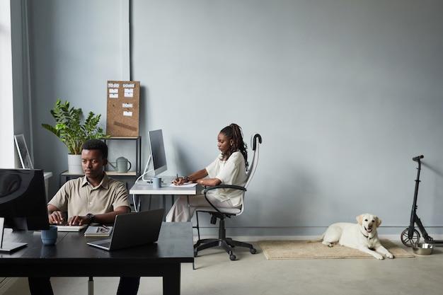 Brede hoekmening op modern kantoorinterieur met hond liggend op de vloer huisdiervriendelijke werkruimte kopieerruimte