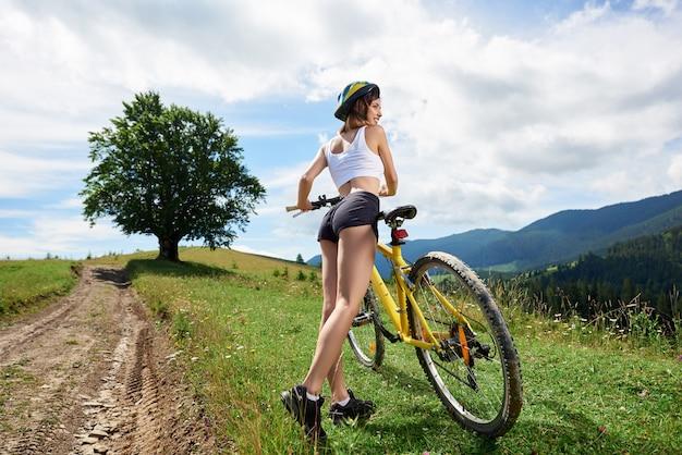 Brede hoekmening van aantrekkelijke vrouwelijke fietser rijden op gele fiets op een landelijke parcours in de bergen. grote boom en bewolkte hemel op de achtergrond. buitensportactiviteiten