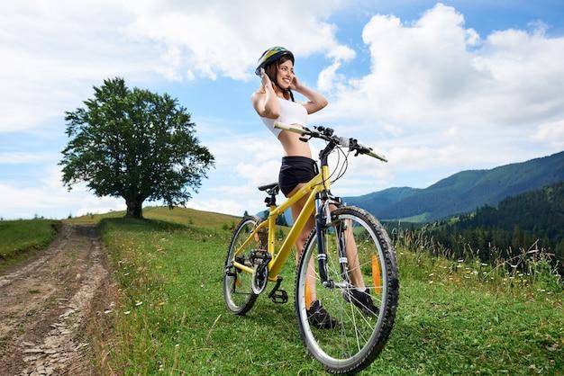 Brede hoekmening van jonge gelukkige meisjesfietser die op gele fiets berijden op een landelijke sleep in de bergen. bergen, grote boom en bewolkte hemel buitensportactiviteit