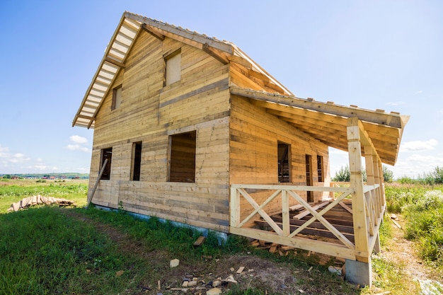 Brede hoekmening van onvoltooide houten ecologische traditionele cottage van natuurlijke timmerhout materialen met steile dak en veranda in aanbouw in groene buurt op blauwe hemel kopie ruimte achtergrond.