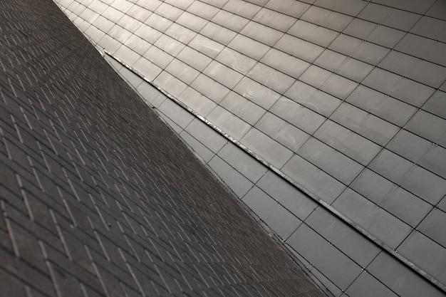 Brede hoekmening van verbinding van grijze bestratingsvlaggang en grijze metaalmuur