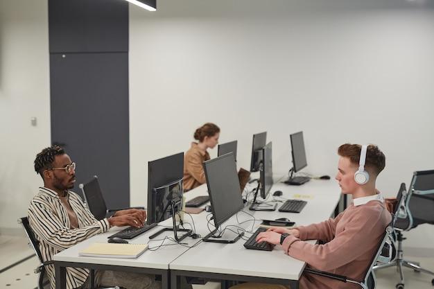 Brede kijkhoek bij een groep jongeren die computers gebruikt terwijl ze in het it-lab op kantoor of op school werken, kopieer ruimte