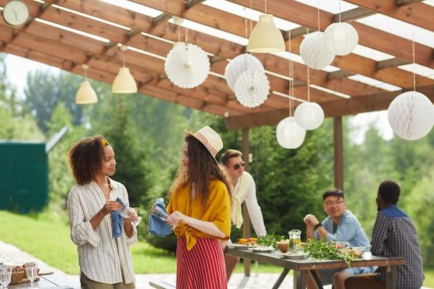 Brede kijkhoek op multi-etnische groep vrienden voorbereiden op zomerfeest op buitenterras