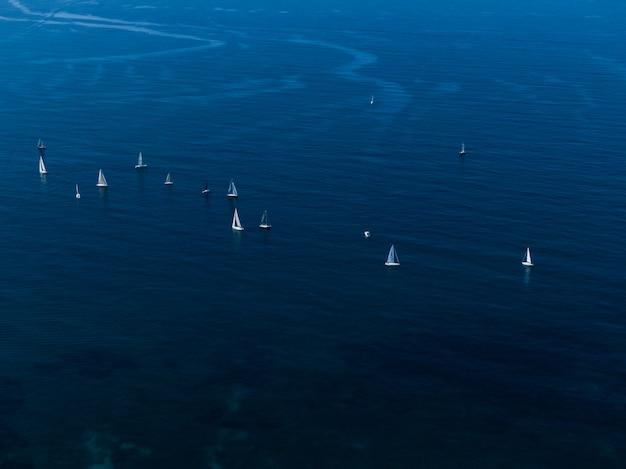 Brede luchtfoto van kleine witte zeilboten drijvend in de oceaan dicht bij elkaar