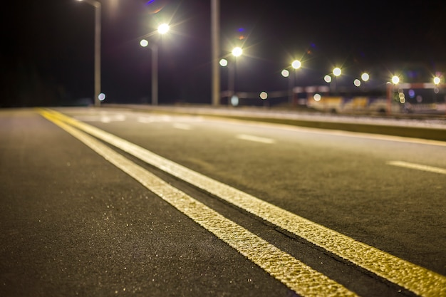 Brede moderne glad leeg verlicht met straatlantaarns asfalt snelweg met helder witte markering teken lijn 's nachts. snelheid, veiligheid, comfortabele reis en professioneel wegenbouwconcept.