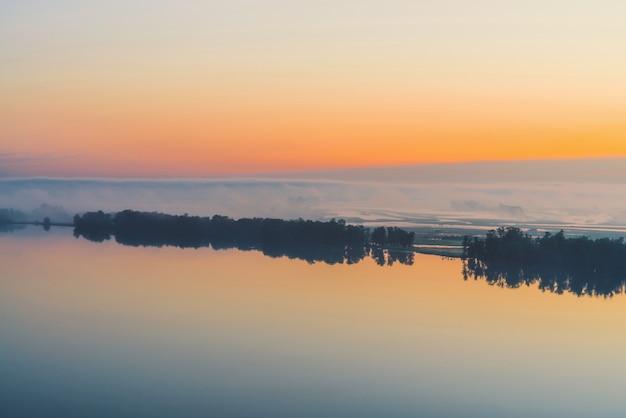 Brede mystieke rivier stroomt langs diagonale kust met silhouet van bomen en dikke mist. gouden gloed in predawnhemel. rustig ochtend sfeervol landschap van majestueuze natuur in warme tinten.