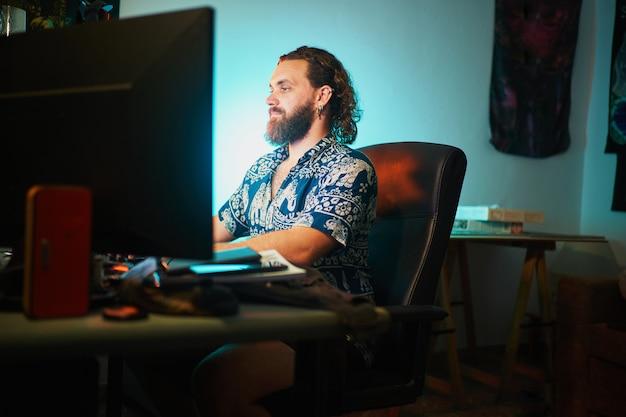 Brede opname van bebaarde man die computer gebruikt tegen groenblauw licht zittend op een stoel