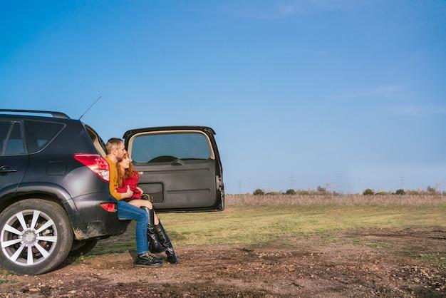 Brede opname van een blank stel dat op een zonnige dag in de kofferbak van een auto in een veld met een blauwe lucht zit