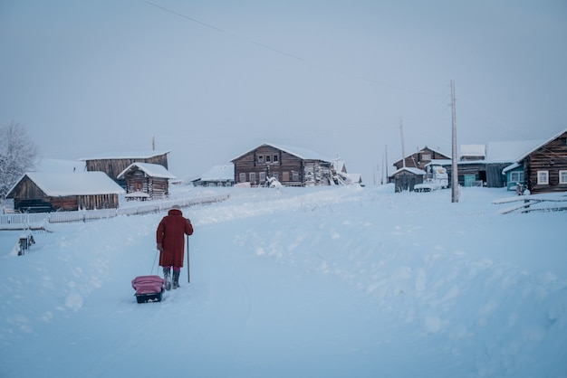 Brede opname van een dorp en een persoon in een rode jas die op een koude dag door de dikke sneeuw loopt
