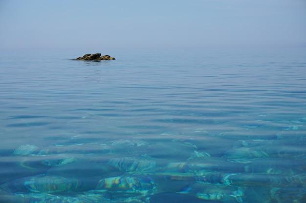 Brede opname van een kalme oceaan met een rotsformatie ver van de kust