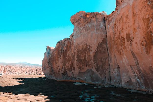 Brede opname van een klif in de woestijn met een helder blauw