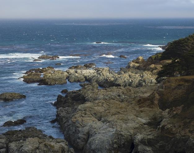 Brede opname van een oceaan met rotsen rond de kust