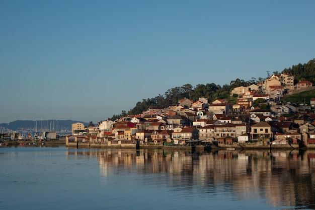 Brede opname van een stad vol huizen op een heuvel aan de kust op een koele dag