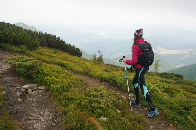 Brede opname van een vrouw die een berg oploopt met volledige uitrusting op een koud en mistig weer