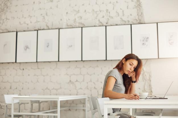 Brede opname van een vrouwelijke werknemer of student die haar dagelijkse werk doet door online prints te ontwerpen of te studeren in een heldere studio-omgeving. onderwijs concept.