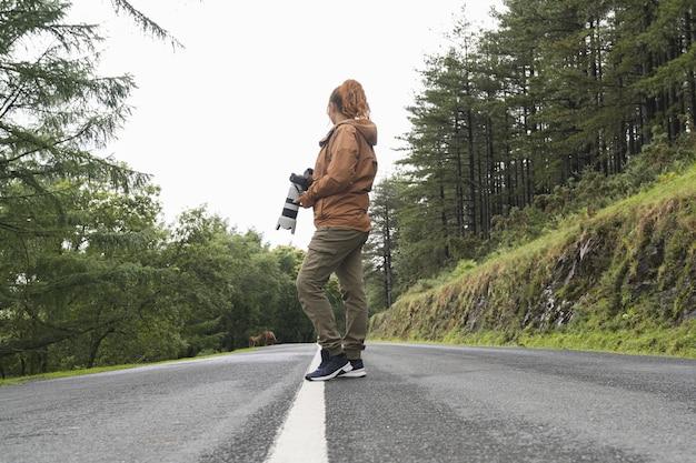 Brede opname van onherkenbare blanke vrouw gekleed in een bruine jas met een camera die midden op een weg van achteren staat en naar het uitzicht kijkt