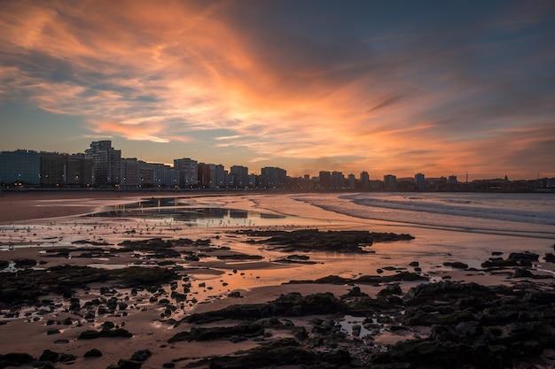 Brede opname van stadsgebouwen in de buurt van de kust in gijon