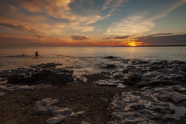 Brede opname van zwemmers in zuid-wales tijdens zonsondergang