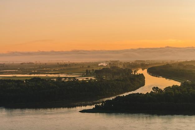 Brede rivier stroomt langs de kust met bos met mist. kanaal van rivier stroomt rond eiland. oranje gloed bij dageraad weerspiegeld in water. kleurrijk ochtend mystiek atmosferisch landschap van majestueuze aard.