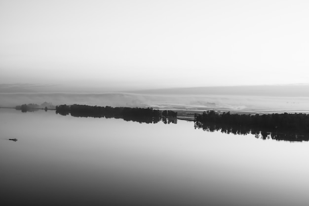 Brede rivier stroomt langs diagonale kust met silhouet van bos en dikke mist in grijstinten
