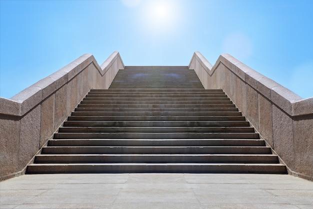 Brede stenen trap. weg tot blauwe lucht in zonnige dag. concept van hoop en mooie toekomst. vrijheid, carrière of succes concept. granieten trappen.