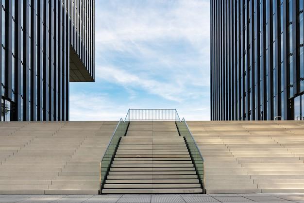 Brede trap tussen twee moderne kantoorgebouwen aan de medienhafen