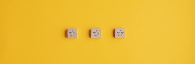 Breed beeld van drie houten blokken met stervorm erop op een rij geplaatst.