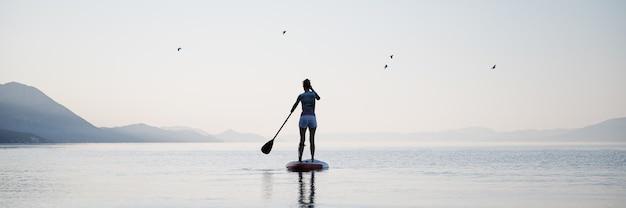 Breed beeld van een jonge vrouw die op sup board peddelt op kalm ochtend zeewater. achteraanzicht.