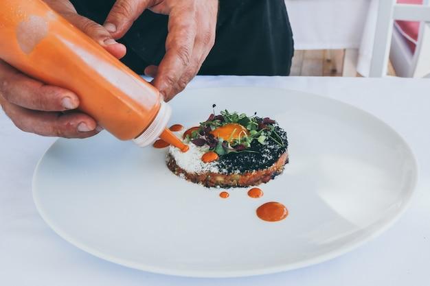 Breed close-upschot van een persoon die ketchup op een gekookte maaltijd op een witte plaat giet