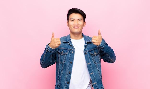 Breed glimlachend gelukkig, positief, zelfverzekerd en succesvol, met beide duimen omhoog