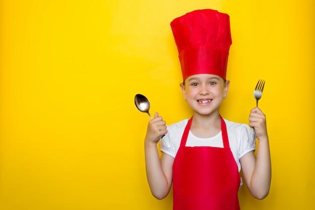 Breed glimlachend meisje die in het kostuum van een rode chef-kok een lepel en een vork op geel houden