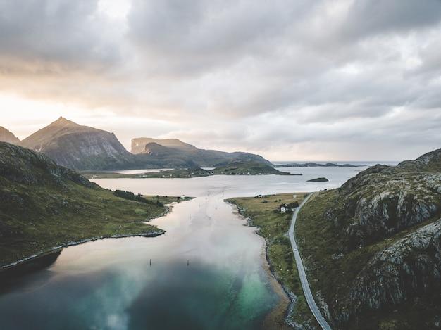 Breed landschapsschot van het overzees dat door bergen onder een rozeachtige hemel met wolken wordt omringd