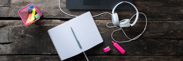 Breed meningsbeeld van open lege blocnote die op rustieke houten bureau door een laptopcomputer met hoofdtelefoons en kleurrijke markeringen ernaast liggen.