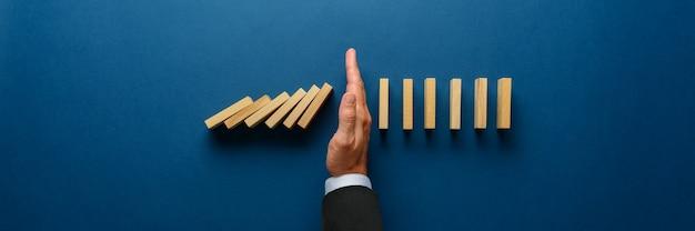 Breed meningsbeeld van zakenmanhand die instortende domino's in een conceptueel beeld tegenhouden. bovenaanzicht over marineblauwe achtergrond.