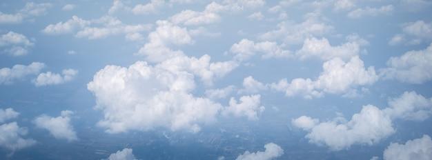 Breed panorama hemelwolken boven de wolken vanuit vliegtuigvenster