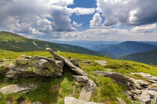 Breed panorama van verlicht door zon bergplateau met groen gras, stukken sneeuw en grote keien op verre bergen onder bewolkte hemel. schoonheid van de natuur, toerisme en reizen concept.