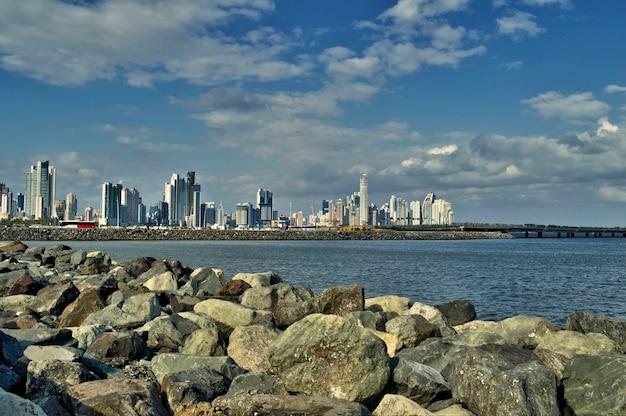 Breed panorama van wolkenkrabbers en de zee van panama city gezien vanaf de kust van casco viejo met rotsen op de voorgrond