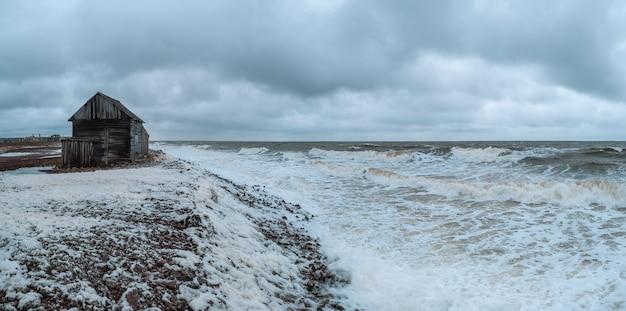 Breed panoramisch uitzicht op een dramatisch zeegezicht met een woeste witte zee en een vissershut aan de kust