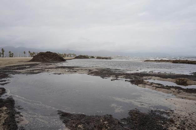 Breed shot van een kust met een stapel zwart zand