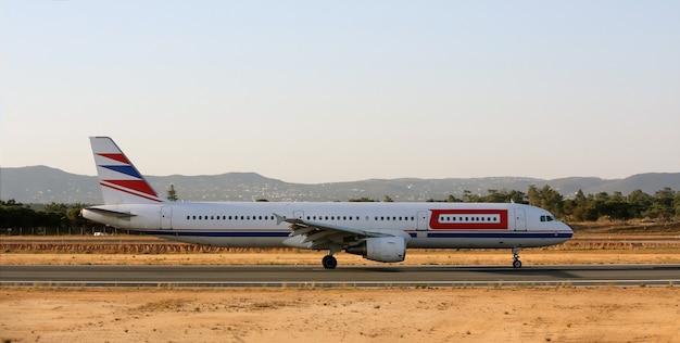 Breed zicht op de zijkant van een commercieel vliegtuig dat op het vliegveld landt.