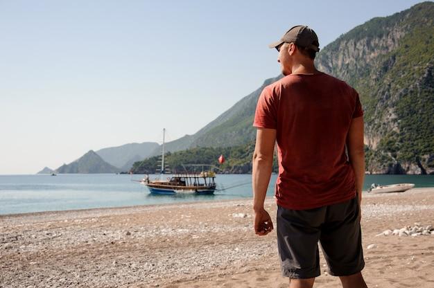 Breedgeschouderde man die zich voordeed op het turkse strand