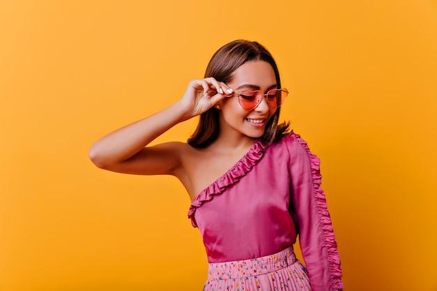 Breekbare, verlegen vrouw van 21 jaar in blouse met blote schouder glimlacht vriendelijk, naar beneden kijkend. close-upportret van stijlvol model op geïsoleerde muur