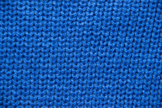 Brei van dichtbij. gekleurde gebreide wol close-up. blauwe achtergrond