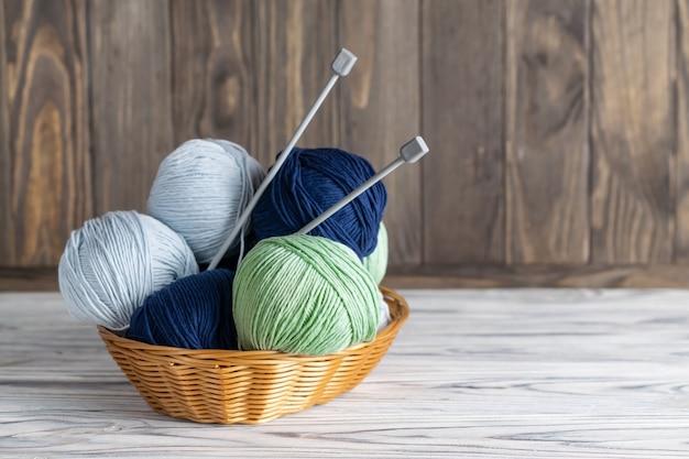 Breiend blauw en groen garen in een mand met naalden op houten