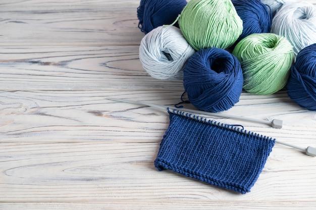 Breiende hobbysamenstelling met blauw en groen garen en naalden op witte houten